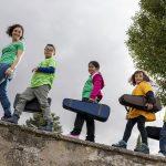 Fila de alumnos con fundas de violín